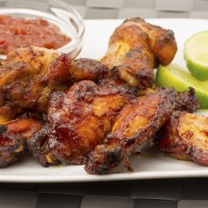 Chicken wings with a tomato dip and lime garnish - studio shot