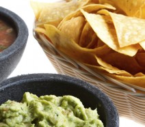 Close shot of fresh Mexican corn chips in a wicker basket, homemade spicy salsa and gourmet guacamole from a nice Mexican restaurant isolated on white